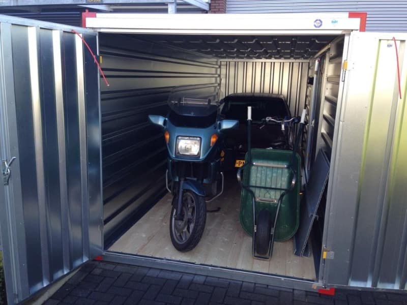 A motorbike and wheelbarrow parked in a steel storage container. The bike is blue and the barrow if green.
