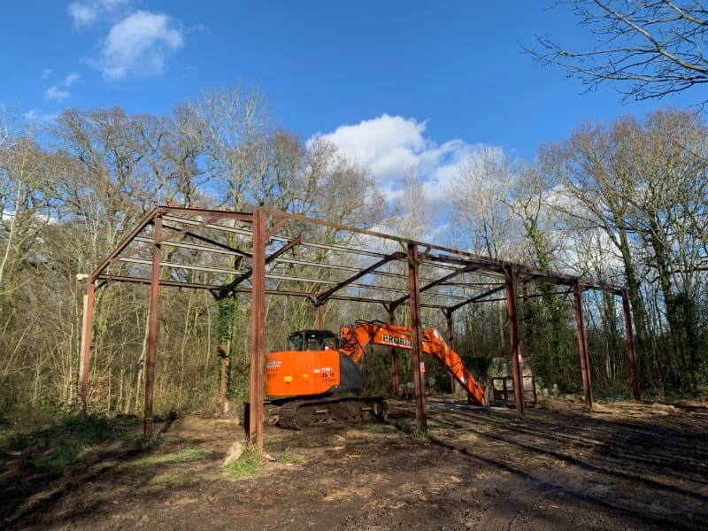 Steel framed farm barn with no roof, sides or ends. Just the frame stands over an orange excavator. The barn is in a woodland setting during winter.