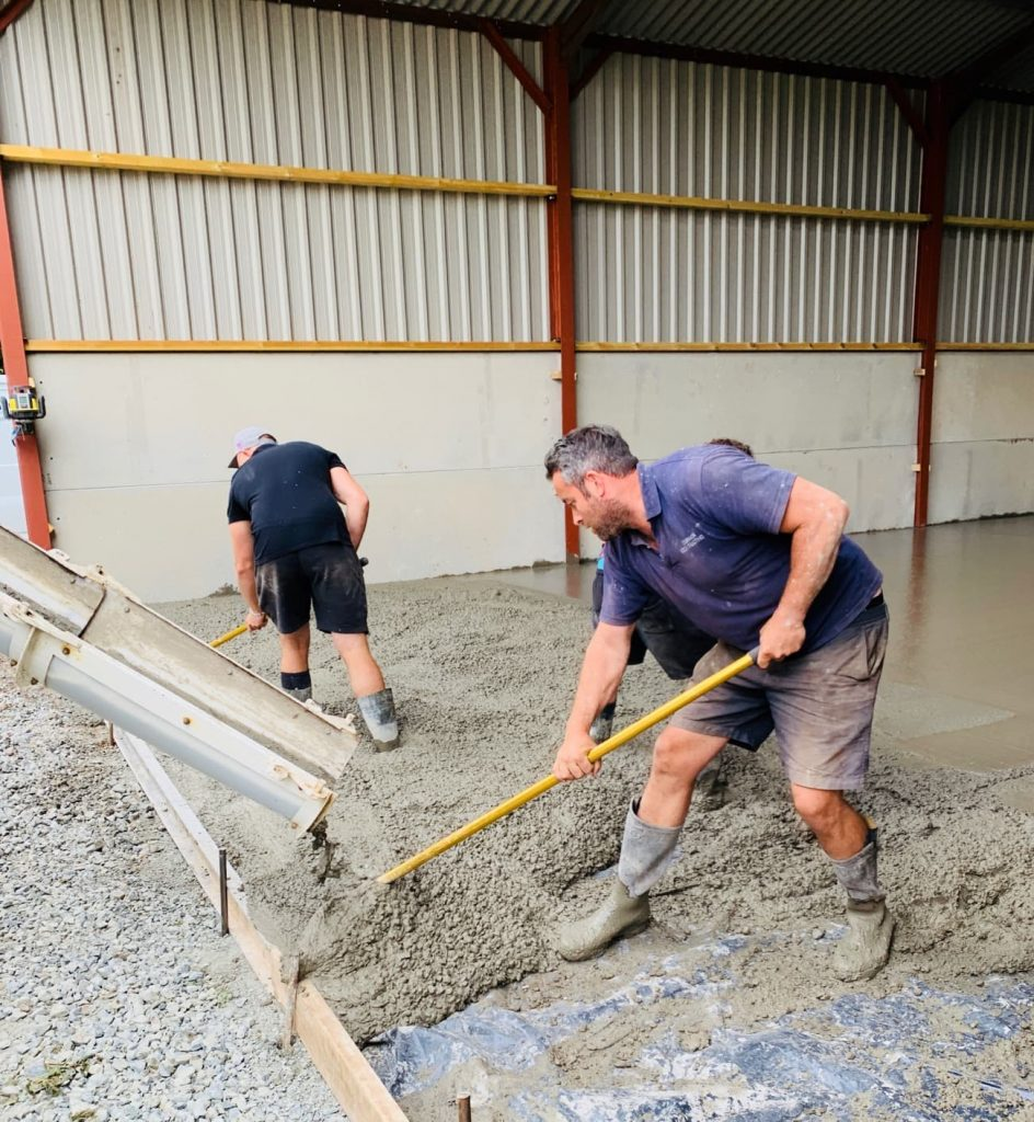 Two men in wellington boots stand in a barn as a lorry pours liquid concrete to make a smooth floor. The men rake the concrete into place.
