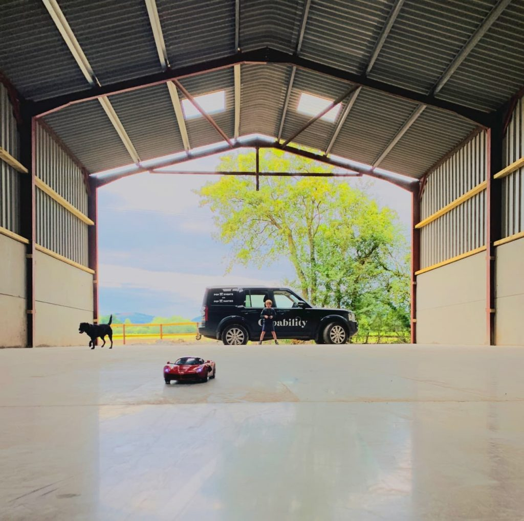 A boy is silhouetted against the open end of a storage barn. He is playing with a toy Ferrari car. A black dog runs after the car.