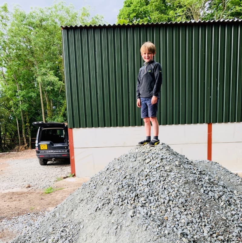 A small boy stands on top of a large pile of stone in front of a green storage barn. The boy is wearing shorts.