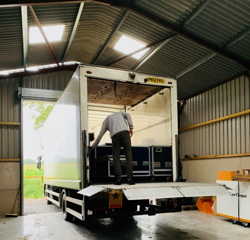 A large white lorry is backed into a storage barn roller shutter door. A man is unloading the lorry via it's tail lift.