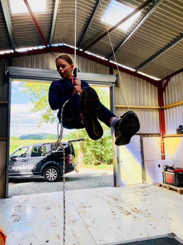 A girl climbs ropes into the roof of a storage barn in front of an open roller shutter door. A Land Rover Discovery is parked in the doorway.