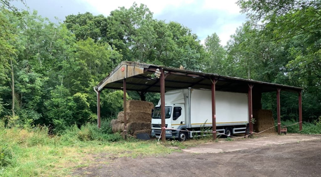 Farm barn with no sides in a wood during the spring. A white lorry sits inside the barn