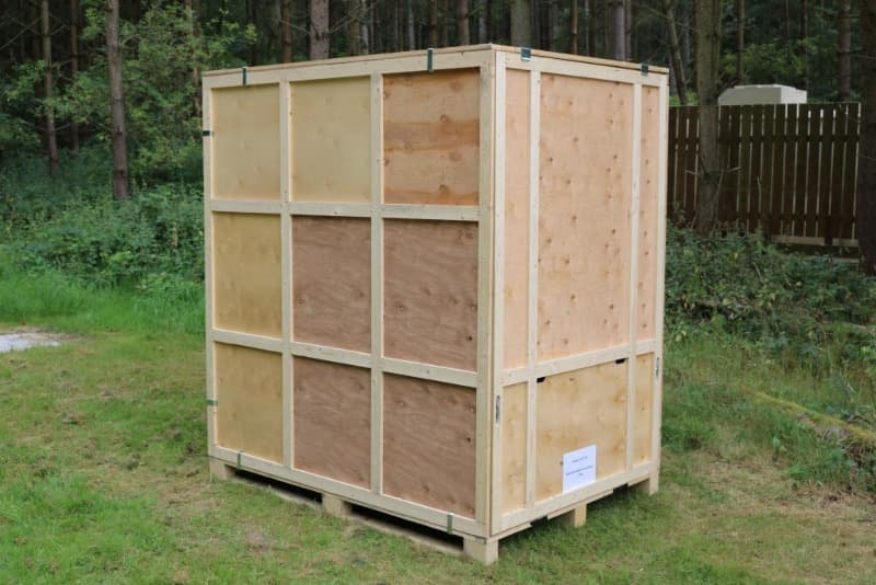 Large wooden storage container stands on the grass in a woodland setting.